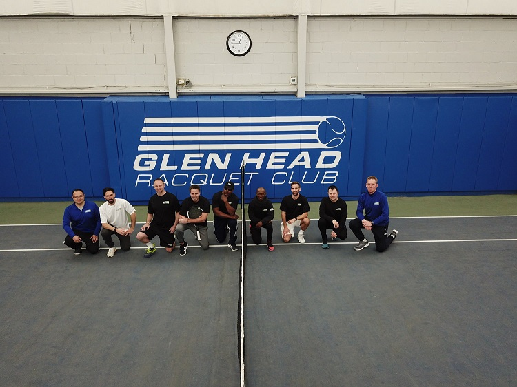 Some of the professional staff and coaches of Glen Head Racquet & Fitness pose for a picture on court.